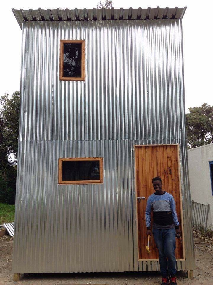 Vuyo next to a mostly finished 2 story shack
